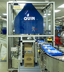Casepacker - case packing equipment from Quin Systems - in operation on a biscuit line.